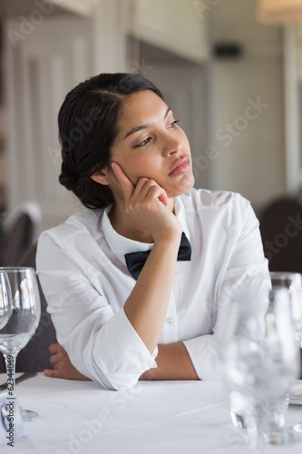 Thoughtful waitress sitting at set table