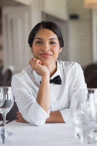 Happy waitress sitting at set table