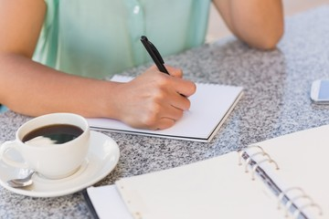 Businesswoman having coffee and planning her week