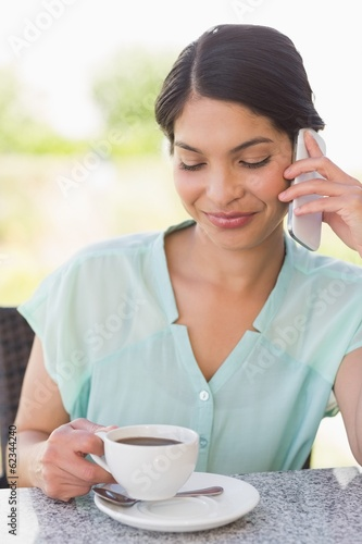 Smiling businesswoman having a coffee talking on phone
