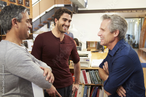 Three Male Architects Chatting In Modern Office Together