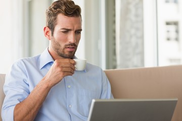 Handsome businessman working on laptop drinking espresso
