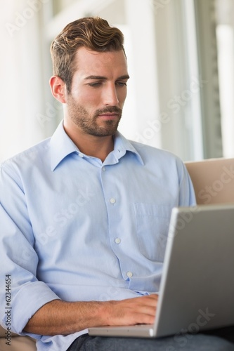 Handsome businessman working on laptop