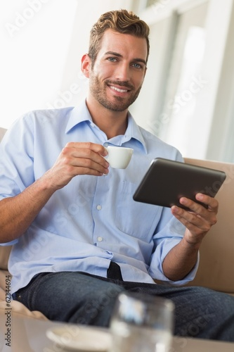 Handsome businessman working on tablet pc drinking espresso