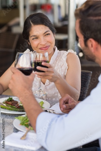 Happy couple on a date drinking red wine
