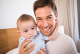 Father sitting on bed with baby son in blue babygro
