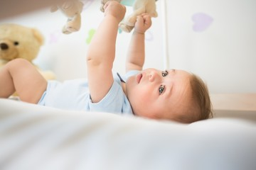 Baby boy lying in crib playing with mobile