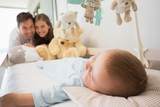 Happy parents watching over baby son sleeping in crib
