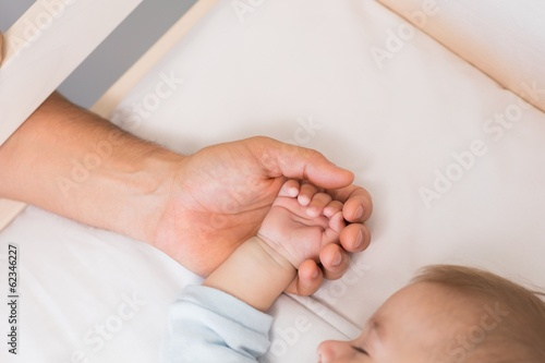 Father holding hand of baby son in crib