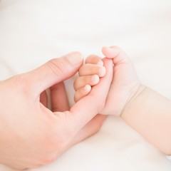 Mother holding baby sons hand