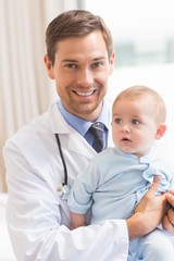 Handsome pediatrician holding baby boy