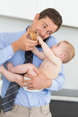 Busy father holding his baby son before work and eating toast