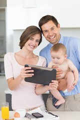 Happy parents using tablet pc with their baby son in the morning