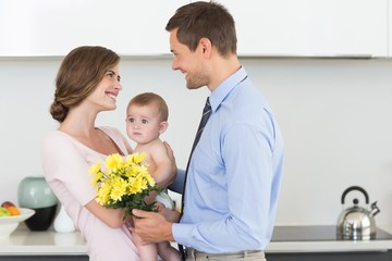 Father giving mother holding baby a bunch of yellow flowers