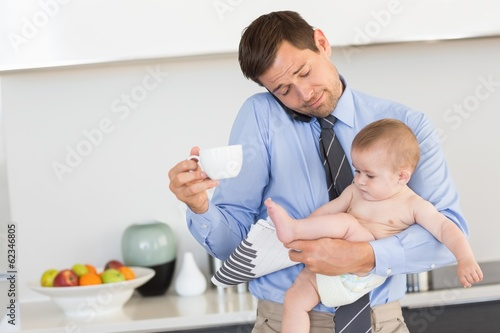Busy father holding his baby son before work