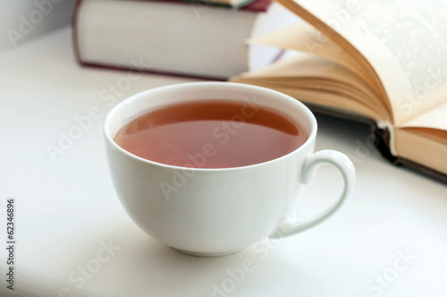 Cup of black tea and some books to read lying on the table