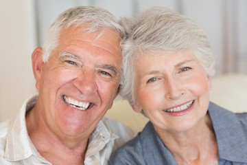 Smiling senior couple sitting on the couch