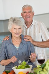 Happy senior couple preparing a salad