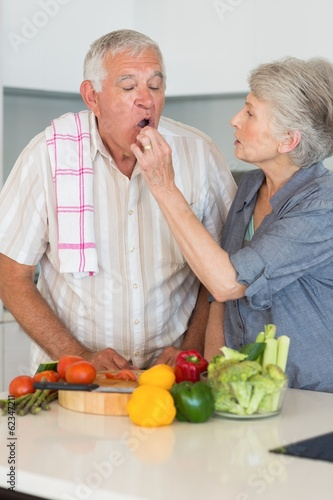 Happy senior couple preparing vegetables