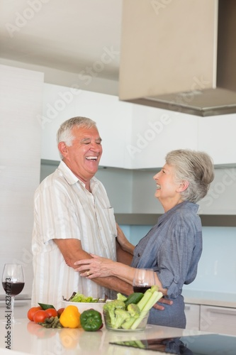 Happy senior couple hugging while preparing a meal