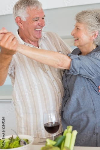 Happy senior couple dancing while preparing a meal
