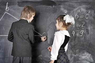 boy and girl writing on blackboard