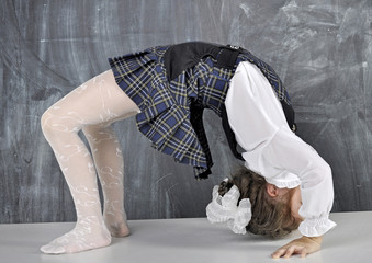 Schoolgirl doing gymnastics on the table