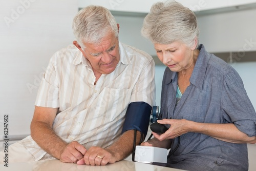 Senior woman checking her husbands blood pressure