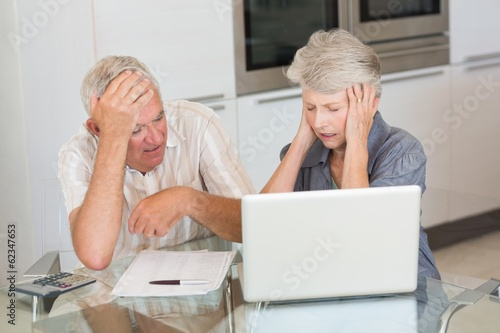 Worried senior couple using the laptop to pay bills