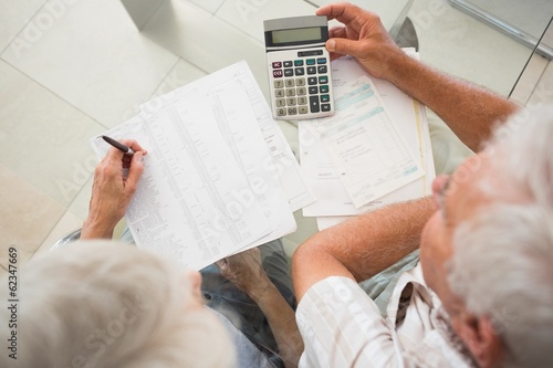 Senior couple using the calculator to pay bills