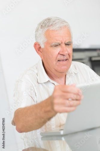 Confused senior man using the laptop at the table