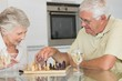 Smiling senior couple playing chess and having white wine