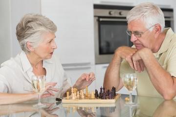 Smiling senior couple playing chess and having white wine