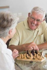 Senior couple playing chess and having white wine