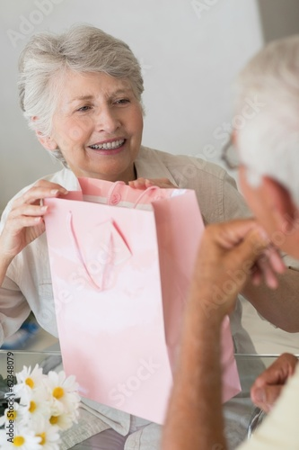 Happy senior woman getting a gift from her partner