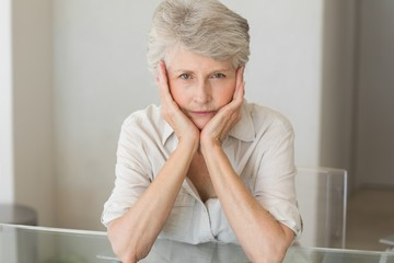 Depressed senior woman sitting at the table