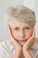 Depressed senior woman looking at camera