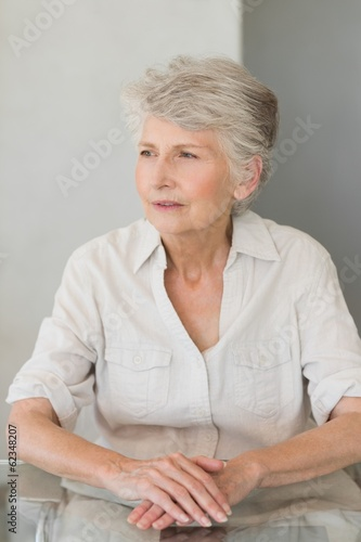 Thoughtful senior woman sitting at the table