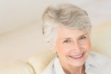 Senior woman sitting on couch smiling at camera