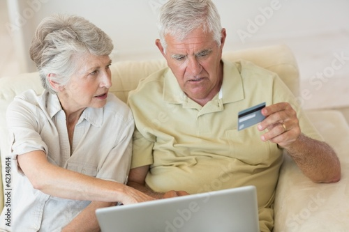 Senior couple using the laptop together to shop online