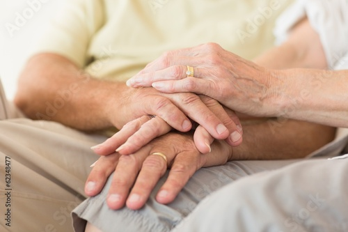 Senior couple sitting on couch holding hands