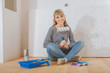 happy smiling female painter sitting on wooden floor and holding