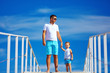 father and son on bridge, sky background