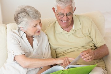 Cheerful senior couple looking at photo album on the couch toget