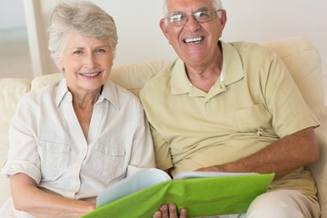 Cheerful senior couple looking at photo album on the couch