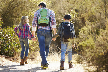 Rear View Of Father And Children Hiking In Countryside