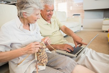 Senior couple sitting on floor knitting and using laptop