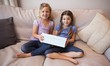 Two young girls sitting with gift box on couch