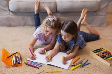 Siblings drawing in the living room