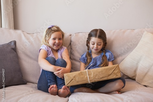 Young girls sitting with gift box on couch